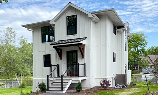 large lake home with white siding and black trim