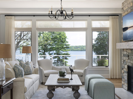 Living room with picture window overlooking lake with chic furniture